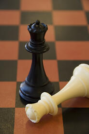 Black queen stands victorious over fallen white queen on chessboard